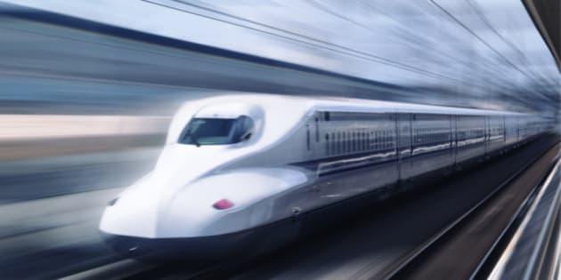 Shinkansen high-speed bullet train N700 series Nozomi passing a platform blurred from motion. Shizuoka, Japan