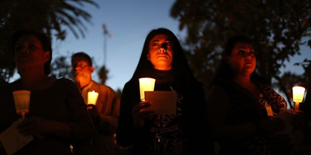 SAN BERNARDINO, CA - DECEMBER 07:  People hold candles as they attend a vigil held at the San Bernardino County Board of Supervisors headquarters to remember those injured and killed during the shooting at the Inland Regional Center on December 7, 2015 in San Bernardino, California. FBI and other law enforcement officials continue to investigate the mass shooting that left 14 people dead and another 21 injured on December 2nd.  (Photo by Joe Raedle/Getty Images)