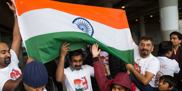 LONDON, ENGLAND - NOVEMBER 13:  Members of the Greater Manchester Malayalee Hindu Community hold up a flag as they arrive by coach to Wembley Stadium to hear Indian Prime Minister Narendra Modi speak during the second day of an official three day visit on November 13, 2015 in London, England. In his first trip to Britain as Prime Minister Modi's visit will aim to develop economic ties between the two countries. In a busy schedule he will speak at Wembley Stadium, lunch with the Queen at Buckingham Palace, address Parliament and stay overnight at Chequers.  (Photo by Rob Stothard/Getty Images)