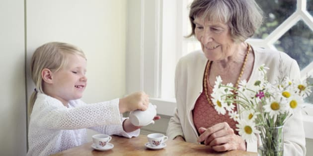 Girl pouring tea into a tea cup and her grandmother sitting beside her