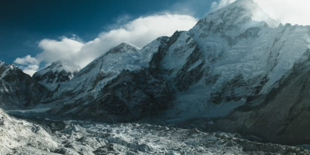 MOUNT EVEREST, NEPAL, FEBRUARY 13, 2015: THe Khumbu Glacier is seen after fresh snowfall near the base of Mount Everest (C, 8848m) and Nuptse (R, 7861m) in the Solu-Khumbu region of Nepal, February 13, 2015. The Solu-Khumbu region is home to the world's highest mountain, Mount Everest (8848m). According to leading researchers, in recent years the landscape and people of the Solu-Khumbu region have come under increasing pressure from raising temperatures and shifting climactic conditions. As well as being home to many of the world's highest mountains, the region holds some of the world's largest and highest glaciers, some of which have begun to show signs of increased and rapid melt. The Khumbu glacier, which lies at the foot of Mount Everest, has in the last decade begun to develop ponds of water on its surface, which scientists say could develop into a much larger lake on the glacierâs surface if warming trends continue.  Recent research indicates that annual mean surface temperature in the Himalaya has increased by 1.5 degrees celsius over pre-industrial temperatures. (Photo by Ed Giles/Getty Images).