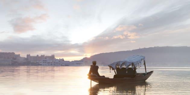 Boat man paddles traditional boat (shikara) in Lake Pichola at sunrise.