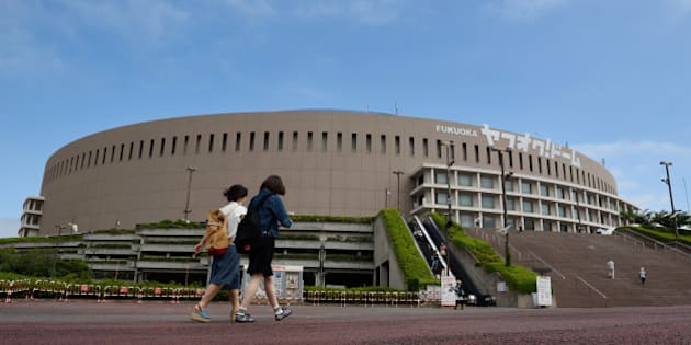 Pedestrians walk past the Yahuoku! Dome, operated by Fukuoka SoftBank Hawks Corp., in Fukuoka, Japan, on Saturday, July 18, 2015. Prices of many products will need to rise at a faster rate than the goal to make up for a drag on the inflation index from distorted housing costs in the gauge, Kiyohiko Nishimura, 62, who heads a government statistics panel, said on July 15. Photographer: Akio Kon/Bloomberg via Getty Images