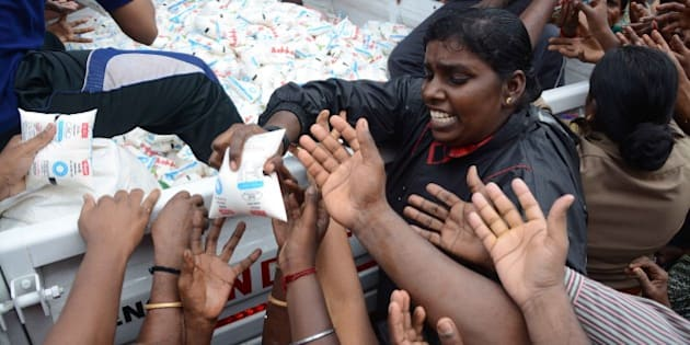 Indian volunteers distribute packets of milk from the back of a vehicle to flood affected residents in Chennai on December 5, 2015.    Thousands of rescuers are racing to evacuate victims of the Tamil Nadu flooding, which has claimed nearly 300 lives since November 9. Weather officials said rainfall in Chennai had diminished since earlier in the week, but parts of the city of 4.6 million people remained submerged.   AFP PHOTO/STR / AFP / STRDEL        (Photo credit should read STRDEL/AFP/Getty Images)