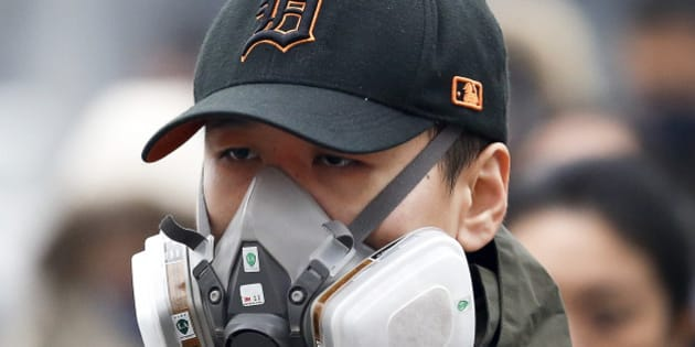 In this Dec. 8, 2015 photo, a man wears a mask to protect himself from pollutants on a heavily polluted day in Beijing.  Episodes of nauseating smog lasting several days has become part of wintertime in Beijing. (AP Photo/Andy Wong)