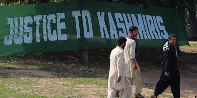 ISLAMABAD, PAKISTAN - OCTOBER 27: Pakistani demonstrators hang a banner written 'Justice to Kashmiris' during a protest against the presence of India in the Himalayan region, at Constitution Avenue where government buildings exist along the road in Islamabad, Pakistan on October 27, 2014. Kashmir is divided between India and Pakistan by a de facto border known as the Line of Control but it is claimed in full by both countries. 27th of October is known as Black Day since the Indian armed forces occupied Jammu and Kashmir territory on 27th October 1947. (Photo by Metin Aktas/Anadolu Agency/Getty Images)