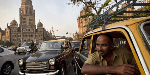 MUMBAI, INDIA - DECEMBER 8: Drivers wait for a passenger in their Premier Padmini taxis outside Chhatrapati Shivaji Station on December 8, 2012 in Mumbai, India. The Padmini, manufactured by Premier Automobiles in India from 1964 to 2000, are disappearing from the street as a result of a government order banning taxis over 25 years old.