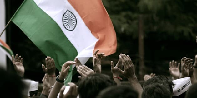 Indian flag waving amidst sea of people celebrating passing of Anna's Jan Lokpal bill.