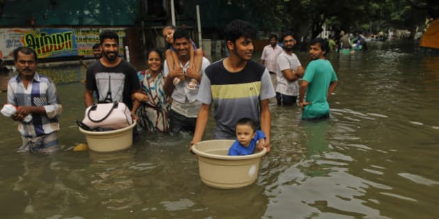 People with their children wade through flood waters in Chennai, India, Thursday, Dec. 3, 2015. The heaviest rainfall in more than 100 years has devastated swathes of the southern Indian state of Tamil Nadu, with thousands forced to leave their submerged homes and schools, offices and a regional airport shut for a second day Thursday.( AP Photo)