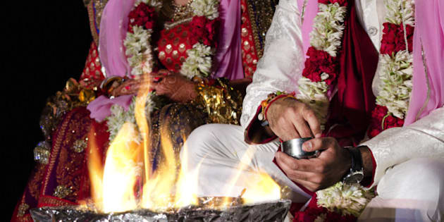 An Indian couple worshipping the fire deity, as a part of the Indian traditional wedding rituals.Fire deity is considered to be a primary witness of a Hindu marriage.