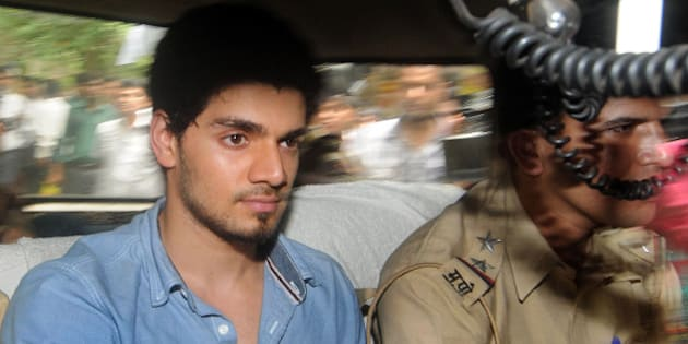 Indian actor Suraj Pancholi, boyfriend of the late Bollywood film actress Jiah Khan, sits inside a police vehicle on his way to a court in Mumbai on June 11, 2013, on suspicion of abetting her suicide after her family found a letter in her room.  Suraj Pancholi, a 22-year-old aspiring actor, was detained on June 10 a week after his girlfriend's body was discovered by her parents at her home.   AFP PHOTO        (Photo credit should read STR/AFP/Getty Images)