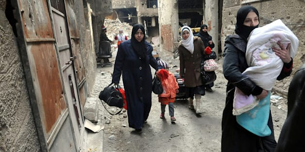 FILE - In this Feb. 4, 2014, file photo released by the Syrian official news agency SANA, residents of the besieged Yarmouk Palestinian refugee camp carry their belongings as they flee the camp, on the southern edge of the Syrian capital Damascus, Syria. Conditions in the camp have deteriorated since Islamic State militants muscled their way into it in early April 2015. The militants are trying to consolidate their hold on the camp. (AP Photo/SANA, File)