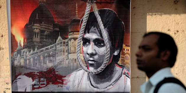 Indian pedestrians walk past a poster depicting the hanging of  Pakistani-born Mohammed Ajmal Kasab, 25, the sole surviving gunman from the 2008 Mumbai attacks outside a railway station in Mumbai on November 26, 2012.  A total of 166 people were killed and more than 300 others were injured when 10 heavily-armed Islamist militants stormed the city on November 26, 2008, attacking a number of sites, including the city's main railway station, two luxury hotels, a popular tourist restaurant and a Jewish centre.  AFP PHOTO/ INDRANIL MUKHERJEE        (Photo credit should read INDRANIL MUKHERJEE/AFP/Getty Images)