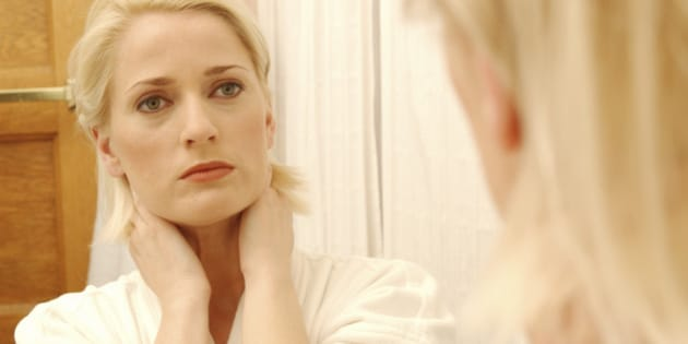 Woman Looking At Her Face In Bathroom Mirror
