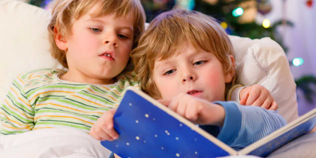 Two little blond sibling boys reading a book in bed near Christmas tree with lights and illumination. Happy family of two brothers.