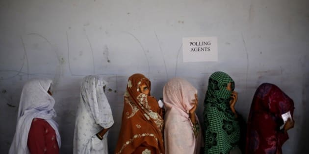 "Indian women voters cover their faces as they stand in a queue to cast their votes  during a re-polling of the parliamentary elections in Rehna village, in the northern Indian state of Haryana, Thursday, May 15, 2014. The Election Commission had ordered re-polling in some polling stations in the state following complaints. Official election results are expected on Friday, but exit polls by at least six major Indian TV stations show the Hindu nationalist Bharatiya Janata Party likely to win enough seats to form a coalition government. Hindi on the wall reads, ""Save the girl child, save the nation.""(AP Photo/Altaf Qadri)"