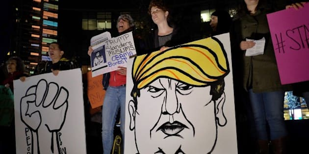 Human rights activists and people from Muslim community display a placard depicting US presidential hopeful Donald Trump during a demonstration in New York on December 10, 2015 in solidarity for Syrian and Iraqi refugees. AFP PHOTO/JEWEL SAMAD / AFP / JEWEL SAMAD        (Photo credit should read JEWEL SAMAD/AFP/Getty Images)