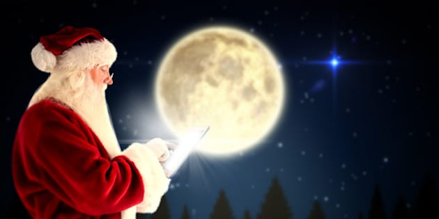 Santa uses a tablet PC against full moon over forest at night