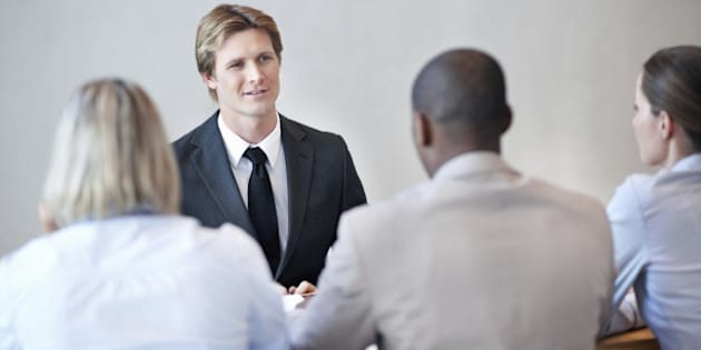 'Smart, male applicant being interviewed by a panel of business people'