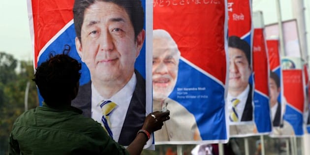 An Indian worker hangs posters of Japan's Prime Minister Shinzo Abe (L) and India's Prime Minister Narendra Modi (R) along a road in Varanasi on December 11, 2015.  Japanese Prime Minister Shinzo Abe will look to seal a deal on building India's first bullet train after he arrived in New Delhi on December 11, for talks with counterpart and conservative soulmate Narendra Modi. Abe will meet Indian business leaders in the capital before taking a tour with Modi on December 12, of India's holiest city of Varanasi and the prime minister's parliamentary constituency.    AFP PHOTO/PRAKASH SINGH / AFP / PRAKASH SINGH        (Photo credit should read PRAKASH SINGH/AFP/Getty Images)