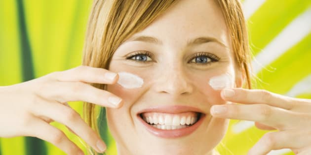Young woman putting cream on face, smiling, portrait