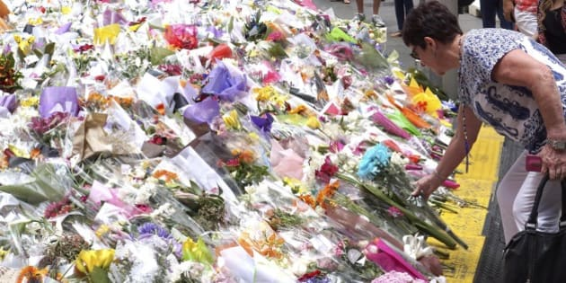 A woman places a floral tribute at a temporary memorial site close to the Lindt Chocolat Cafe in Sydney, Australia, Friday, Dec. 19, 2014. An Iranian-born, self-styled cleric with a lengthy criminal history, burst into a downtown Sydney cafe on Monday wielding a shotgun, taking 17 people hostage. The siege ended 16 hours later when police stormed into the cafe to free the captives, two of whom were killed in a barrage of gunfire, along with the gunman. (AP Photo/Rob Griffith)