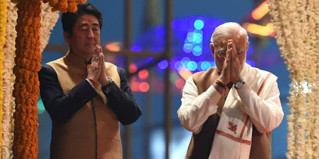 Japan's Prime Minister Shinzo Abe (L) and India's Prime Minister Narendra Modi (R) pray as they attend the evening 'Aarti' ritual on the banks of the River Ganges at Varanasi on December 12, 2015. Japan will build India's first bullet train under a sweeping tally of agreements made following talks in New Delhi on December 12, deepening a partnership Prime Minister Narendra Modi said would 'shape the course of Asia'.  Later the two leaders visited the Indian premier's parliamentary constituency of Varanasi, India's holiest city.  AFP PHOTO / PRAKASH SINGH / AFP / PRAKASH SINGH        (Photo credit should read PRAKASH SINGH/AFP/Getty Images)