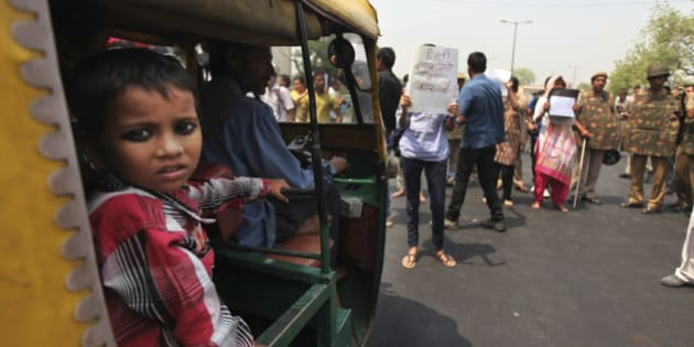 An Indian boy looks out an autorickshaw as it is stopped by protesters outside Delhi Police headquarters during a protest against the rape of a 5-year-old girl in New Delhi, India, Saturday, April 20, 2013. Officials say the child is in serious condition after being raped and tortured by a man who held her in a locked room in India's capital for two days. Police say the girl went missing Monday and was found Wednesday by neighbors who heard her crying in a room in the same New Delhi building where she lives with her parents. (AP Photo/Altaf Qadri)