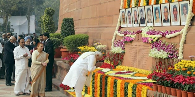 Indian Prime Minister Narendra Modi (R) pays his respects on the 13th anniversary of the 2001 attack on Parliament in New Delhi on December 13, 2014.  The 2001 Indian Parliament attack left 14 people - five terrorists, six Delhi Police personnel, two watch and ward staff and a gardener - dead and increased tensions between India and Pakistan.  AFP PHOTO        (Photo credit should read STR/AFP/Getty Images)