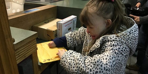 CORRECTS YEAR TO 2015, NOT 2013 - Safyre Terry, 8, opens a gift Wednesday, Dec. 9, 2015, at a post office near her home in Rotterdam, N.Y.  Safyre, who lost her father and three younger siblings and was burned over 75 percent of her body in a May 2013 house fire, has been receiving cards and gifts from across the country since her custodial aunt posted a photo of her on Facebook with a message saying she'd like to get cards for a Christmas tree display stand. The post has been shared tens of thousands of times, and a crowd funding site has generated more than $177,000 for the family. (AP Photo/Mary Esch)