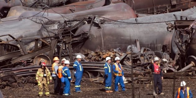 File- In this July 6, 2013 file photo, workers stand before mangled tanker cars at the crash site of the train derailment and fire in Lac-Megantic, Quebec, Canada. On the tranquil bank of the Columbia River in Vancouver, Wash., just across from Portland, Ore., regulators are weighing the fate of what could become the Pacific Northwest's largest crude oil train terminal: it would receive daily shipments of up to 360,000 barrels of oil via four trains a day rolling through iconic river communities and into the crowded Portland/Vancouver metro area, each train 120 cars and more than a mile long.  (AP Photo/Ryan Remiorz, Pool, File)