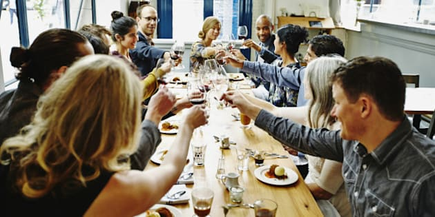 Smiling group of friends toasting at dinner party in restaurant