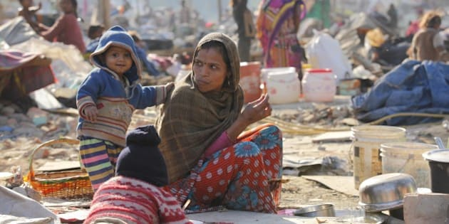NEW DELHI, INDIA - DECEMBER 13: Stranded people sit near their demolished shanties after more than 500 slums were demolished last night in an anti-encroachment drive conducted by the Indian Railways at Shakur Basti, on December 13, 2015 in New Delhi, India. Slum residents created uproar after a child was found dead. They alleged that the child had died in the anti-encroachment drive. Railway denied the allegations, saying that the death of the child occurred in one of the slums and had nothing to do with the removal of encroachments. (Photo by Arvind Yadav/Hindustan Times via Getty Images)