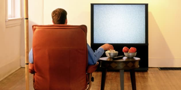 Rear view of a man sitting in an armchair and watching television