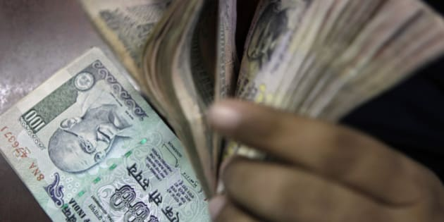 An Indian counts rupee notes at a foreign exchange shop in New Delhi, India, Thursday, Aug. 29, 2013. The rupee rose to 66.85 against the dollar Thursday after a record low of 68.85 per dollar on Wednesday. (AP Photo/Tsering Topgyal)