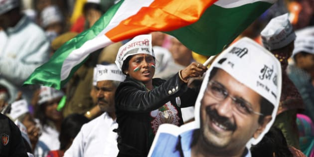 A supporter of Aam Aadmi Party, or Common Man's Party, waves an Indian flag  next to a cut-out of party leader Arvind Kejriwal during his swearing-in ceremony as chief minister of Delhi in New Delhi, India, Saturday, Feb. 14, 2015. The AAP, headed by the former tax official who had remade himself into a champion for clean government, won 67 of the 70 seats in recent elections. Kejriwal and the party he created routed the country's best-funded and best-organized political machine and dealt an embarrassing blow to Prime Minister Narendra Modi. (AP Photo/Altaf Qadri)