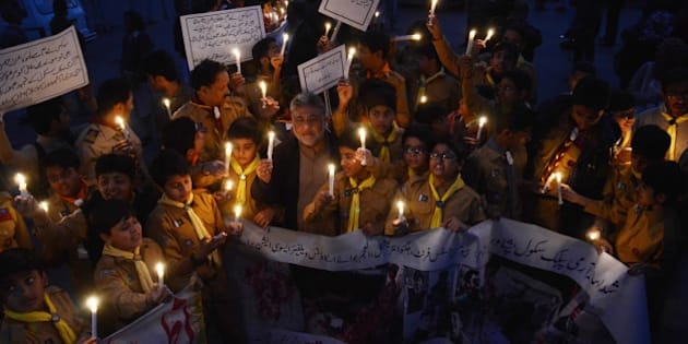LAHORE, PUNJAB, PAKISTAN - 2015/12/15: Pakistani students,teachers and civil society activists  hold lit candles during a vigil to pay tribute to the victims of the Peshawar school massacre of December 16, 2014, the deadliest terror attack in Pakistan's history. (Photo by Rana Sajid Hussain/Pacific Press/LightRocket via Getty Images)