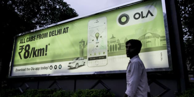 A pedestrian walks past an advertisement for the Ola ride-hailing service and application, owned by ANI Technologies Pvt., in New Delhi, India, on Saturday, Sept. 19, 2015. Ola, the operator of an Indian taxi-hailing app, will lease cars to boost the number of vehicles in its network to stave off competition from Uber Technologies Inc. Photographer: Dhiraj Singh/Bloomberg via Getty Images