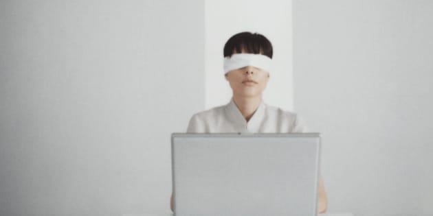 Blindfolded woman sitting behind laptop