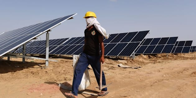 TO GO WITH: Climate-warming-COP21-India-energy-solar, FOCUS by Annie Banerji In this photograph taken on August 23, 2015, an Indian engineer walks past solar panels at the under construction Roha Dyechem solar plant at Bhadla some 225 kms north of Jodhpur in the western Indian state of Rajasthan.  Under a blistering sun, workers install a sea of solar panels in a north Indian desert as part of the government's clean energy push --- and its trump card at upcoming climate change talks in Paris.  AFP PHOTO / MONEY SHARMA        (Photo credit should read MONEY SHARMA/AFP/Getty Images)