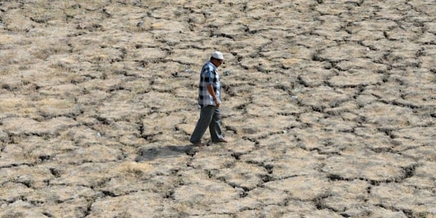 This photo taken on May 28, 2015 shows an Indian man walking across the dried-out bed of Lake Ahmad Sar as extreme heat conditions prevail in Ahmedabad. Hospitals in India battled May 28 to treat victims of a blistering heatwave that has claimed more than 1,700 lives in just over a week -- the highest number recorded in two decades. AFP PHOTO / Sam PANTHAKY        (Photo credit should read SAM PANTHAKY/AFP/Getty Images)