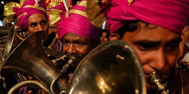 Members of an Indian wedding band play brass instruments during a religious procession for the Hindu festival Ganesh Chaturthi in New Delhi on September 24, 2015. AFP PHOTO / CHANDAN KHANNA        (Photo credit should read Chandan Khanna/AFP/Getty Images)
