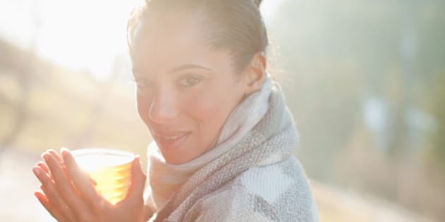 Portrait of smiling woman in scarf drinking cider