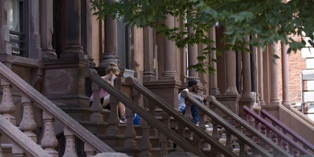 Brownstone residents sit on steps in central Harlem, New York, U.S., on Sunday, Aug. 10, 2014. Developers and buyers are betting Harlem apartment prices, which lag behind the rest of Manhattan by about 50 percent, still have room to grow. The neighborhood's transformation over the past two decades already has enriched succeeding waves of homeowners, as condo prices almost doubled over the past decade and more than tripled over the past 20 years, according to the Furman Center for Real Estate and Urban Policy at New York University. Photographer: Jin Lee/Bloomberg via Getty Images