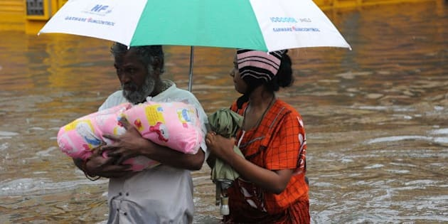 An Indian family wade through floodwaters in Chennai on December 2, 2015.   India has deployed troops to Tamil Nadu and closed the main airport there after heavy rains worsened weeks of flooding that has killed nearly 200 people in the southern coastal state. Thousands of rescuers carrying diving equipment, inflatable boats and medical equipment were battling to evacuate victims across the flooded state, officials said.    AFP PHOTO/STR / AFP / STRDEL        (Photo credit should read STRDEL/AFP/Getty Images)