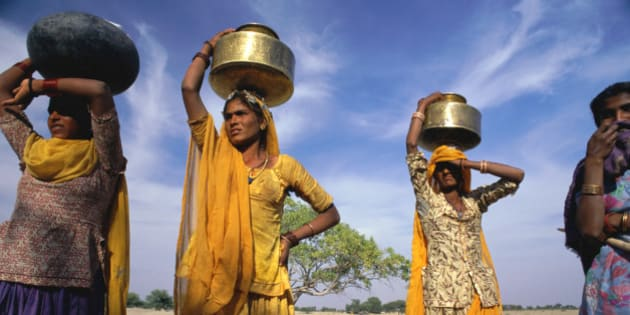 India, Rajasthan, three tribeswomen collecting water in brass jars