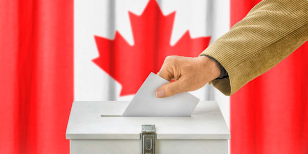 Man putting a ballot into a voting box - Canada