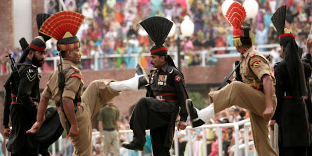 Indian Border Security Force soldiers and Pakistan Rangers soldiers, in black uniform, march during 'Beating the Retreat' or a flag lowering ceremony at the joint border check post of Wagah, India, Wednesday, July 11, 2007. (AP Photo/Aman Sharma)