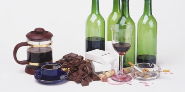 Coffee pot, cup of black coffee, chocolate, cigarettes, glass and bottles of wine and corks.