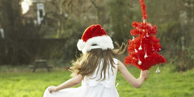 Girl dancing in field with Christmas tree